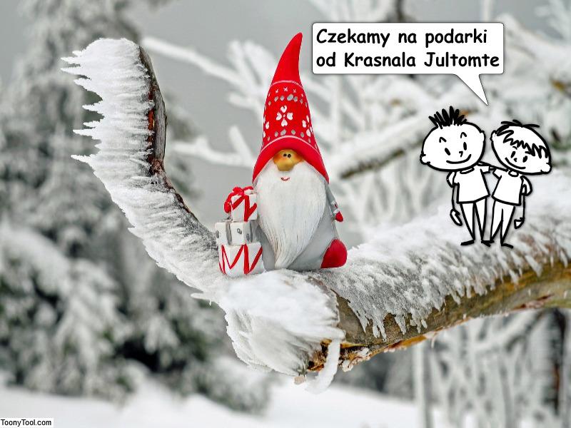 """Zdjęcie przedstawia krasnala w czerwonej czapce siedzącego na ośnieżonej gałązce choinki. Obok są dwie postacie chłopców i napis """"czekamy na prezent od Krasnala Jultomte"""""""